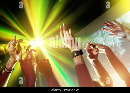 Party concept with hands and light rays - Stock Photo