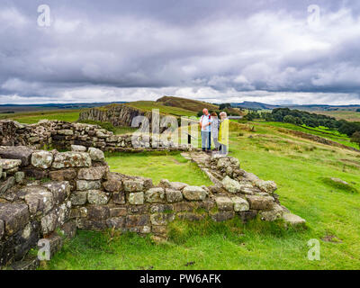 13 August 2018: Hadrian's Wall, Northumberland - Group of walkers at Turret 45A on Hadrians' Wall near Walltown Crags under a dramatic sky. - Stock Photo