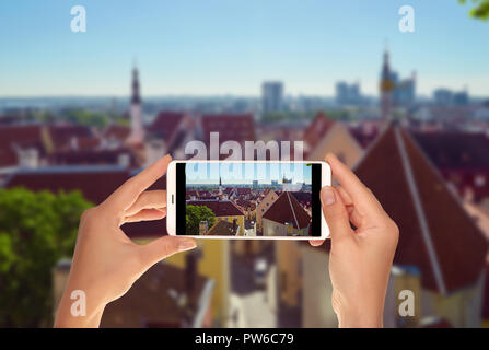 A tourist is taking a photo of Tallinn from the top in a clear sunny day on a mobile phone - Stock Photo