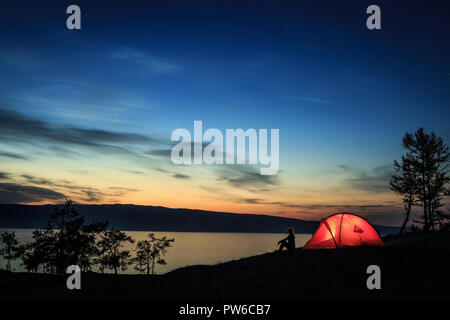 Silhouette of a girl near a tent - Stock Photo