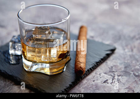 Glass of whiskey with ice cubes and cigar - Stock Photo