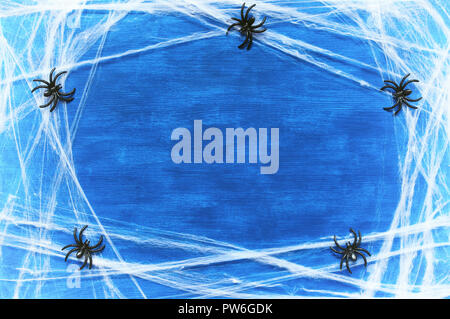 Halloween background. Spider web and spiders as the symbols of Halloween on the dark blue wooden background. Halloween festive card with free space fo - Stock Photo