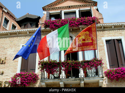 The European Union, the Italian and the flag of Venice all fly outside an hotel in the Italian city of Venice. - Stock Photo