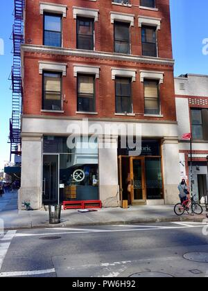 Exterior of typical old brick building showing external fire escapes, housing WeWork offices, Grand Street, New York, NY, USA. - Stock Photo