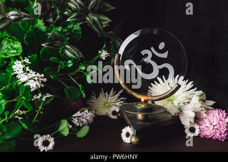 Green Candle on Om Altar with Mixed Flowers and Foliage - Stock Photo