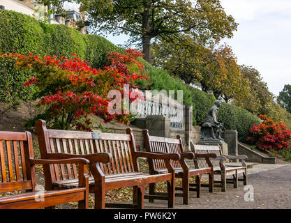 Wooden benches in Princes Street Gardens with red maple leaf colours at Scottish American war memorial, Edinburgh, Scotland, UK - Stock Photo