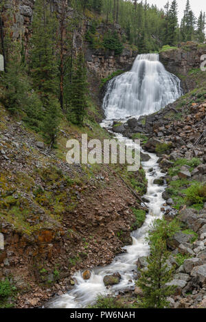 Rustic Falls Drains into River on overcast day - Stock Photo