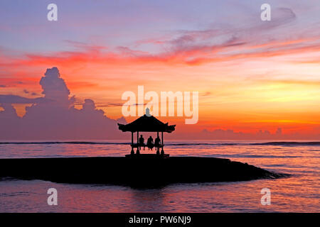 Three people sitting in a Balinese Pagoda on Sanur Beach at Sunrise, Sanur Beach, Bali, Indonesia - Stock Photo