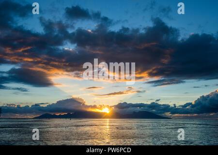 Dramatic sunset over Moorea, Papeete, Tahiti - Stock Photo