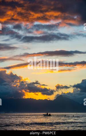 Silhouette of boat, dramatic sunset over Moorea, Papeete, Tahiti - Stock Photo