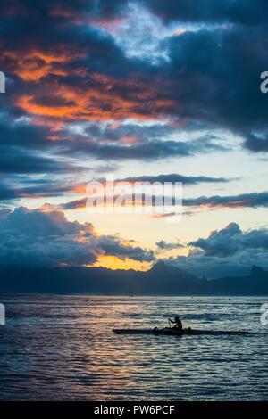 Silhouette of kaykaer, dramatic sunset over Moorea, Papeete, Tahiti - Stock Photo
