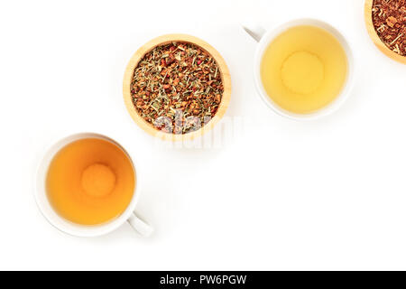 An overhead photo of tea, two cups and two bowls with loose tea leaves, on a white background with copy space - Stock Photo