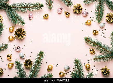 Pastel Pink Christmas Festive frame of fir branches, golden balls and confetti. - Stock Photo