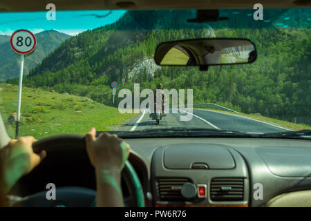 The girl drives along the asphalt road in the Altai Mountains along a serpentine road chasing two people on a motorcycle, and near the road there is a - Stock Photo
