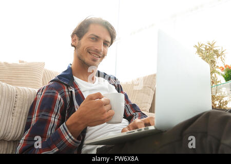 young man with laptop holding a cup sitting on the floor near the sofa - Stock Photo
