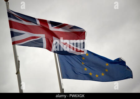 british uk union flag and eu flag flying in dark stormy sky england uk - Stock Photo