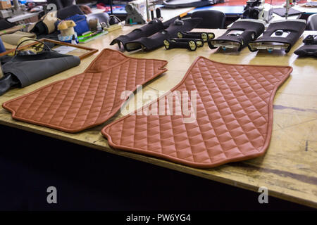 Car 3D handmade rugs with diamond-shaped stitching threads of brown color from genuine leather for front passengers of a vehicle in an interior design - Stock Photo