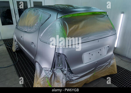 Full painting of a silver car in the back of a hatchback, some parts of which are protected by paper from splashes of paint droplets in a car body rep - Stock Photo