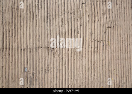 Close up outdoor view of a concrete striped surface. Abstract design of a rough grey texture with shadows. Detail of a modern building wall with rugged elements. Pattern of white and gray lines. - Stock Photo