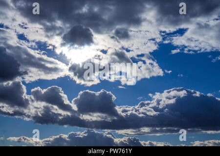 Cumulus clouds on blue sky background highlighted with sun - Stock Photo