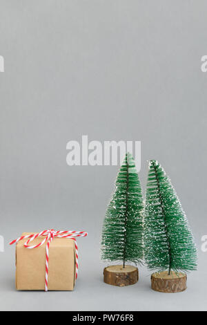 One gift box wrapped in craft paper tied with red white ribbon Christmas trees on grey background. New Year corporate presents shopping concept. Poste - Stock Photo