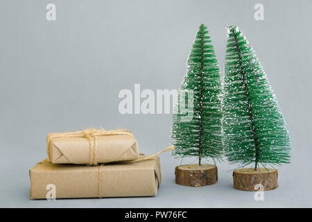 Stacked gift boxes wrapped in craft paper tied with twine Christmas trees on grey background. New Year corporate presents shopping concept. Poster ban - Stock Photo