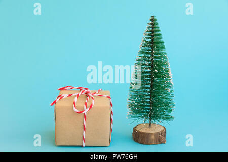 One gift box wrapped in craft paper tied with red white ribbon Christmas trees on light blue background. New Year corporate presents shopping concept. - Stock Photo