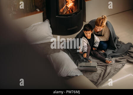 Young family sitting near fireplace looking at laptop. Son pointing at laptop to show something interesting to his mother at home. - Stock Photo