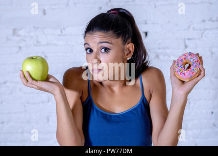 Beautiful young woman doubting having to make choice between apple and doughnut in healthy unhealthy food, detox eating, calories and diet concept. - Stock Photo