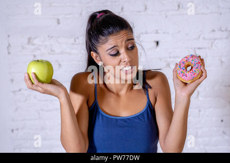 Beautiful young woman tempted having to make choice between apple and doughnut in healthy unhealthy food, detox eating, calories and diet concept. - Stock Photo