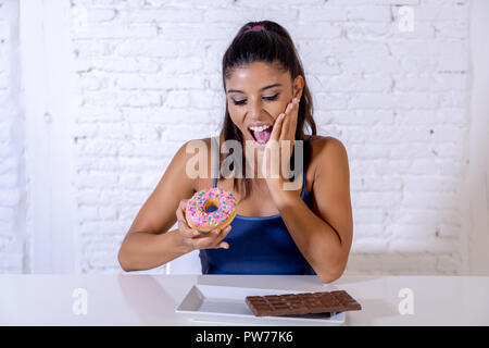 Young attractive latin woman sitting at table about to eat chocolate and doughnuts looking excited and happy in no more diet, sugar and chunky unhealt - Stock Photo
