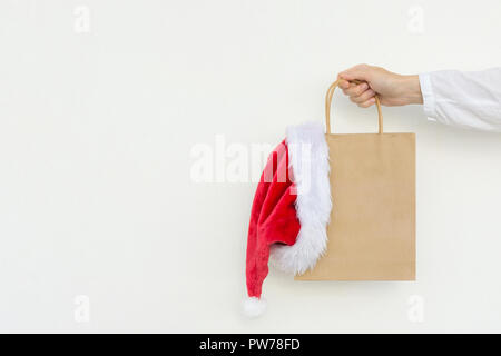 Young caucasian woman holds in hand empty blank mock up brown craft paper bag with hanging santa claus hat on white wall background. Christmas New Yea - Stock Photo