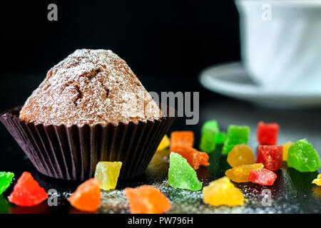 Freshly baked muffins with candied fruit on a black table - Stock Photo