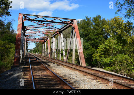 Looking down the tracks at a steel trestle bridge over the Tar River in Rocky Mount, North Carolina. - Stock Photo