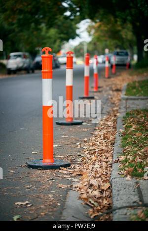 A line of orange and white traffic bollards on an autumn leafy suburban street. - Stock Photo