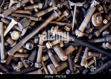 A collection of nuts and bolts, long and short. new and old in all sorts and sizes. - Stock Photo