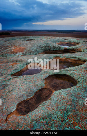 Shallow rock pools aka as gnamma holes by the aboriginals filled with water after recent rain on top of Pildappa Rock, Eyre Peninsula South Australia - Stock Photo