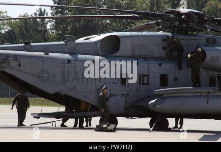 Marines assigned to Marine Heavy Helicopter Training Squadron 302 perform after flight inspections on a CH-53E Super Stallion at Marine Corps Air Station New River, N.C., Sept. 22, 2017. HMHT-302 celebrated the end of the 2017 fiscal year by flying eight helicopters in formation over their squadron. HMHT-302 is assigned to Marine Aircraft Group 29, 2nd Marine Aircraft Wing. - Stock Photo