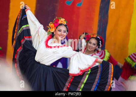 Portland, OR / USA - May 7 2016: Beautiful woman in a traditional latino costume dancing at the cinco de mayo celebration. - Stock Photo