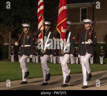 Marines with the U.S. Marine Corps Color Guard march onto center walk during a retirement ceremony for Lt. Gen. John E. Wissler, outgoing commander of Marine Corps Forces Command, at Marine Barracks Washington D.C., Sept. 22, 2017. Before Marine Corps Forces Command, Wissler served as commanding general of III Marine Expeditionary Force. He is retiring after 39 dedicated years of service to the Corps. - Stock Photo
