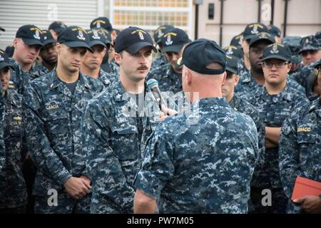 SASEBO, Japan (September 25, 2017) Mineman 1st Class Zachary Able, from Brandon, Miss., assigned to Avenger-class mine countermeasure ship USS Pioneer (MCM 9), speaks with Vice Adm. Tom Rowden, commander, Naval Surface Forces, during a question and answer session of an all-hands call on the pier of commander, Fleet Activities Sasebo. Rowden is visiting Fleet Activities Sasebo, home of U.S. 7th Fleet's forward-deployed amphibious ships, to better understand forward-deployed readiness challenges and to discuss the role of the new Naval Surface Group Western Pacific organization. - Stock Photo