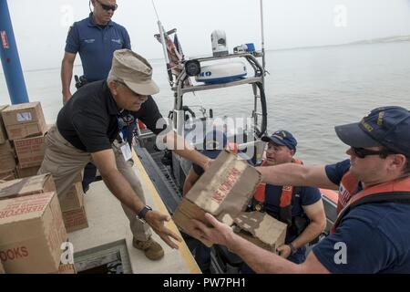 U.S. Coast Guardsmen assigned to the USCGC Heriberto Hernandez (WPC 1114), a Fast Response Cutter homeported in San Juan, Puerto Rico, delivers food near the port of Ponce, Puerto Rico, Sept. 27, 2017. - Stock Photo