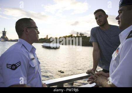 PEARL HARBOR (Sept. 27, 2017) Joint Base Pearl Harbor-Hickam (JBPHH) Service Members explain the history of the USS Arizona to Blake Griffin, basketball player for the Los Angeles Clippers during a tour of the memorial, Sept. 27. While on Oahu for their pre-season training camp, the entire LA Clippers basketball team, coaches, and staff took part in a tour of the USS Arizona Memorial. Along with the team, service members from all branches of the military met at Merry Point Landing, located on JBPHH, to board a vessel which took them to the memorial. - Stock Photo