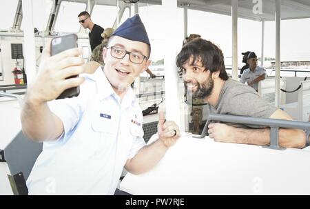 PEARL HARBOR (Sept. 27, 2017) Miloš Teodosić, basketball player for the Los Angeles Clippers pauses for a photo with a  Joint Base Pearl Harbor-Hickam (JBPHH) Service Member, Sept. 27. While on Oahu for their pre-season training camp, the entire LA Clippers basketball team, coaches, and staff took part in a tour of the USS Arizona Memorial. Along with the team, service members from all branches of the military met at Merry Point Landing, located on JBPHH, to board a vessel which took them to the memorial. - Stock Photo