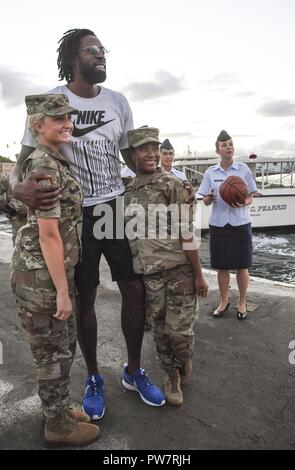 PEARL HARBOR (Sept. 27, 2017) DeAndre Jordan, basketball player for the Los Angeles Clippers pauses for a photo with Joint Base Pearl Harbor-Hickam (JBPHH) Service Members, Sept. 27.  While on Oahu for their pre-season training camp, the entire LA Clippers basketball team, coaches, and staff took part in a tour of the USS Arizona Memorial. Along with the team, service members from all branches of the military met at Merry Point Landing, located on JBPHH, to board a vessel which took them to the memorial. - Stock Photo