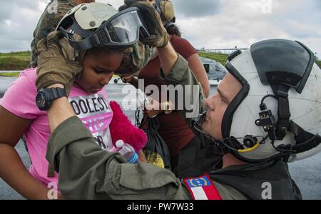 DOMINICA (Sept. 28, 2017) Naval Aircrewman (Helicopter) 2nd Class Nicholas Glass, assigned to Helicopter Sea Combat Squadron (HSC) 22 aboard to the amphibious assault ship USS Wasp (LHD 1), prepares a child for evacuation following the landfall of Hurricane Maria. Dominica residents are being evacuated to local airports and then to the nearby islands of Martinique and Guadalupe. The Department of Defense is supporting the United States Agency for International Development (USAID), the lead federal agency, in helping those affected by Hurricane Maria to minimize suffering and is one component o - Stock Photo
