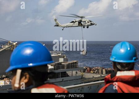 CARIBBEAN SEA (Sept. 28, 2017) Sailors aboard the amphibious assault ship USS Kearsarge (LHD 3) observe as an MH-60 Sea Hawk helicopter transfers pallets of supplies from the fast combat support ship USNS Supply (T-AOE 6) during replenishment-at-sea for continuing operations in Puerto Rico. Kearsarge is assisting with relief efforts in the aftermath of Hurricane Maria. The Department of Defense is supporting the Federal Emergency Management Agency, the lead federal agency, in helping those affected by Hurricane Maria to minimize suffering and is one component of the overall whole-of-government - Stock Photo
