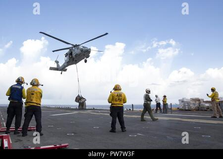CARIBBEAN SEA (Sept. 28, 2017) Sailors aboard the amphibious assault ship USS Kearsarge (LHD 3) observe as an MH-60 Sea Hawk helicopter drops pallets of supplies onto the flight deck during a replenishment-at-sea with the fast combat support ship USNS Supply (T-AOE 6) for continuing operations in Puerto Rico. Kearsarge is assisting with relief efforts in the aftermath of Hurricane Maria. The Department of Defense is supporting the Federal Emergency Management Agency, the lead federal agency, in helping those affected by Hurricane Maria to minimize suffering and is one component of the overall  - Stock Photo
