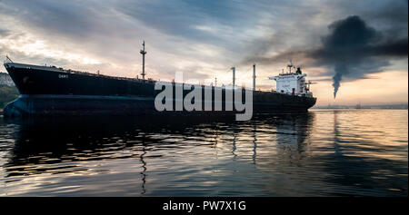 Havana, Cuba. 15th June, 2011. The oil tanker Dart departs from the port early in morning as smoke bellows from the Nico Lopez oil refinery in Havana, - Stock Photo