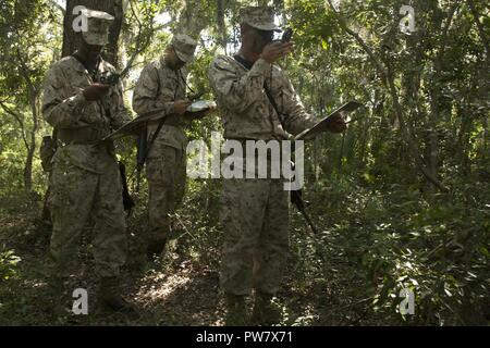 U.S. Marine Corps Recruits with Delta Company, 1st Battalion, Recruit Training Regiment, use compass techniques to reach their next plot point at Elliot's Beach on Marine Corps Recruit Depot, Parris Island, S.C., Sept. 25, 2017.  The Land Navigation Course teaches recruits how to properly navigate unfamiliar terrain. - Stock Photo